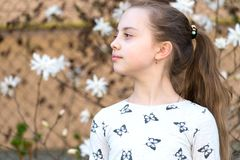 Little girl on floral blossom in spring. Child with blossoming flowers outdoor. Beauty kid with fresh look and long hair. Spring,. Easter and holidays royalty free stock image
