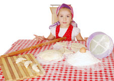 Little girl with flour and rolls Stock Image