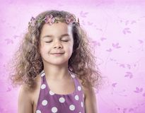 Little girl in flower crown with eyes closed on pink background stock image