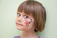 Little girl with flower face paint Stock Photos