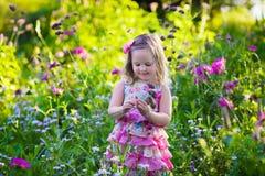 Little girl in flower garden Stock Photography