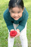 Little girl with flower headband holding red rose in hands. Stock Image
