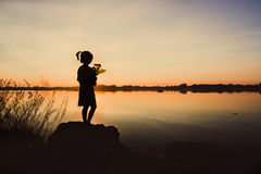 Little girl with a flower in his hand. Give someone, Silhouette Stock Photos