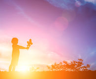 Little girl with a flower in his hand. Give someone, Silhouette Royalty Free Stock Photo