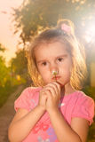Little girl with flower in sunset rays of sun Royalty Free Stock Image