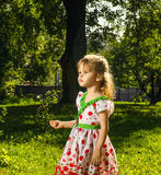Little girl with a flower of white clover in hand Royalty Free Stock Photography