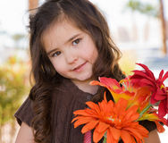 Little girl with flowers. Outdoors portrait of a happy little girl with flowers Royalty Free Stock Photography