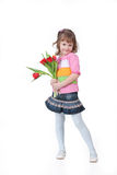 Little Girl With Flowers. Little smiling girl holding the flowers on isolated background Stock Photo
