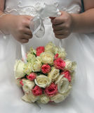 Little Girl and Flowers. Young girl's hands holding a beautiful bouquet of tiny pink, white and yellow roses background showing detail of girls white dress Royalty Free Stock Image