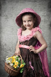 Little girl with flowers. Photo in retro style, the little girl with a basket flowers Royalty Free Stock Photo