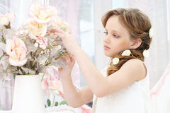Little girl with flowers. Small beautiful girl in white dress holding flowers Stock Images