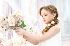 Little girl with flowers. Small beautiful girl in white dress holding flowers Royalty Free Stock Photos