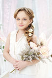 Little girl with flowers. Small beautiful girl in white dress holding flowers Royalty Free Stock Image