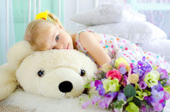 Little girl with flowers embracing big teddy bear Stock Photography