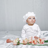 Little girl and flowers. Little girl sitting on silk sheets lie at the feet of flowers Royalty Free Stock Photography