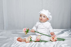 Little girl and flowers. Little girl sitting on silk sheets lie at the feet of flowers Stock Photos