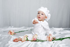 Little girl and flowers. Little girl sitting on silk sheets lie at the feet of flowers Stock Images