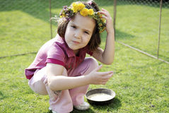 Little girl with flowers thinking Royalty Free Stock Photo