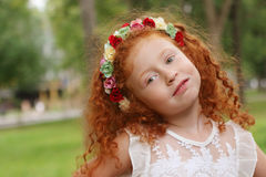 Little girl with flowers wreath poses in summer park, shal Royalty Free Stock Images