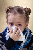 Little girl with the flu blowing her nose Royalty Free Stock Photos