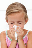 Little girl with the flu blowing nose. Closeup Stock Photos