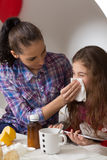 Little girl with flu, cold or fever at home. Fever, cold and flu concepts. Little girlblowing her nose in tissue while her mother sitting near her and helping Stock Photo