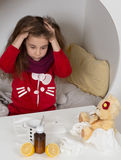 Little girl with flu, cold or fever at home. Fever, cold and flu concepts. Sick girl looking fed up with her illness. Gilr sittin on bed and combing her hair Stock Image
