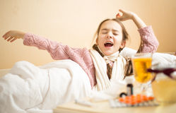 Little girl with flu yawning in bed at morning Stock Photography
