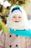 Little girl in a fluffy scarf and coat laughs in the background. Trees Royalty Free Stock Photography