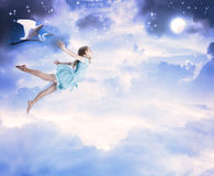 Little girl flying into the blue night sky. With white egret