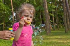 Little girl flying bubble Stock Image