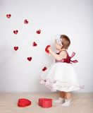 Little girl with flying hearts in studio Royalty Free Stock Image