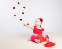 Little girl with flying hearts in studio Stock Photo