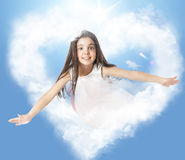 Little girl flying through a heartshaped cloud Stock Images