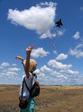 Little Girl Flying Kite. Little girl flying a kite in meadow with clouds and blue sky Stock Images