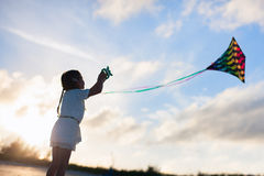 Little girl flying a kite. On beach at sunset Stock Photography