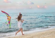 Little girl with flying kite on beach at sunset Stock Images