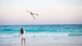 Little girl with flying kite on tropical beach at sunset. Kid play on ocean shore. Child with beach toys. Little girl flying a kite on beach at sunset stock footage