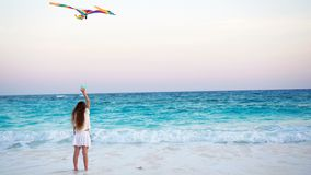 Little girl with flying kite on tropical beach at sunset. Kid play on ocean shore. Child with beach toys. Little girl flying a kite on beach at sunset stock video