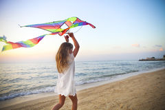 Little girl with flying kite on tropical beach at sunset. Little running girl with flying kite on tropical beach at sunset Stock Image