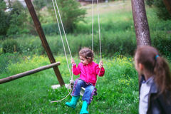 Little girl flying on swing in countryside. Childhood, Freedom, Royalty Free Stock Image