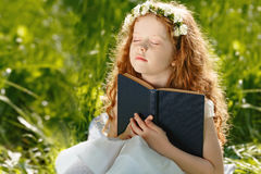 Little girl folded her hand with praying, dreaming in park outdo royalty free stock images