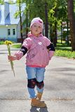 The little girl folded her lips with a bow and holds a bouquet of dandelions. stock photos