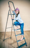 Little girl on a folding ladder Royalty Free Stock Photo