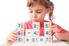 Little girl folds equalizations from cube Royalty Free Stock Photo