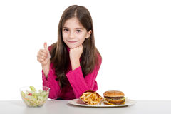 Little girl with food. Little girl thumb up for healthy food Royalty Free Stock Photo