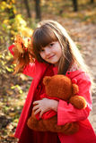 Little girl in forest with maple leaves and bear Royalty Free Stock Images