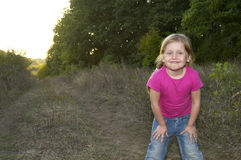 Little girl in the forest. Little girl standing on the path in the summer forest Royalty Free Stock Images