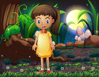 A little girl in the forest wearing a yellow dotted dress Stock Images