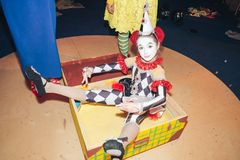 A little girl in the form of harlequin, sitting in a suitcase depicting the frozen figure of a doll. stock photo